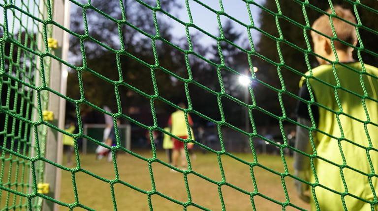 Un enfant se tient debout dans le but lors d'un match de football.
