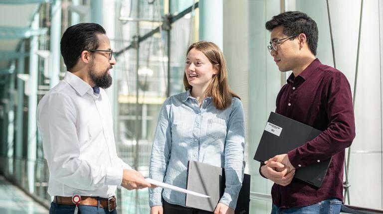 Drei junge Berufstätige, die in einem Gang miteinander reden