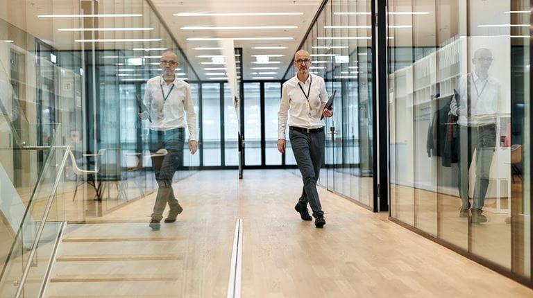 Adrian Zuercher, directeur de la recherche, traverse le site et découvre son image reflétée dans les murs de verre