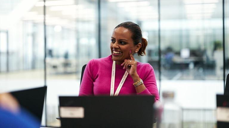 Une femme en pull rose sourit lors d'une réunion