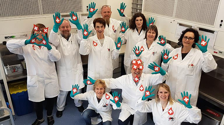 CSL Behring employees posing for a photo while holding paper cut outs of red blood drops with white crosses on them